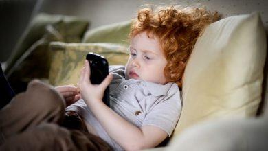 Young child using phone 390x220 - خطوة جديدة من آبل لتقليل إدمان الأطفال للآيفون بإضافة تحكمات أبوية على الجوال