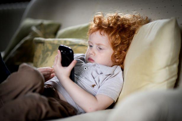 Young child using phone - خطوة جديدة من آبل لتقليل إدمان الأطفال للآيفون بإضافة تحكمات أبوية على الجوال